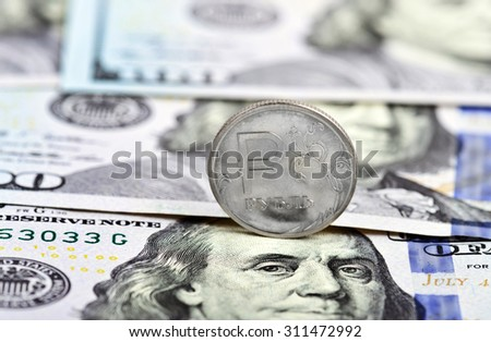 coin one ruble against the background US dollars - stock photo
