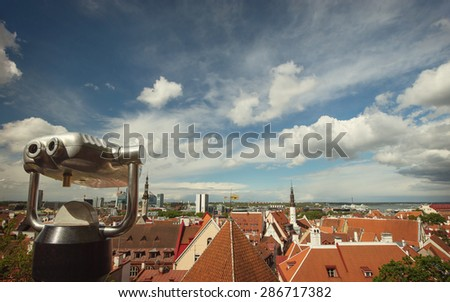 Coin Operated Binocular viewer over European city skyline on blue sky and beautiful clouds background - stock photo