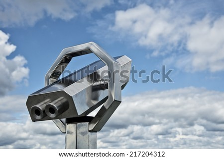 coin operated  telesecope in front of a blue cloudy sky - stock photo