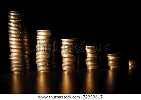 coin stack on black bacground. dramatic light used - stock photo