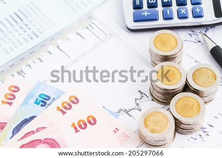 coins and banknote on graph paper - stock photo