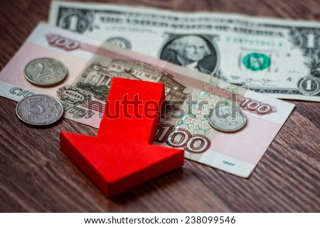 Coins and banknotes of russian roubles on us dollar bill. Devaluation of the Russian rouble. - stock photo