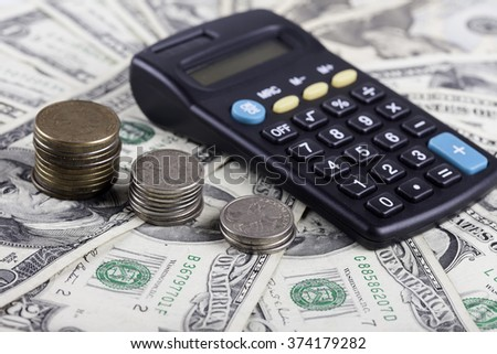 coins and calculator on the background of dollar banknotes - stock photo