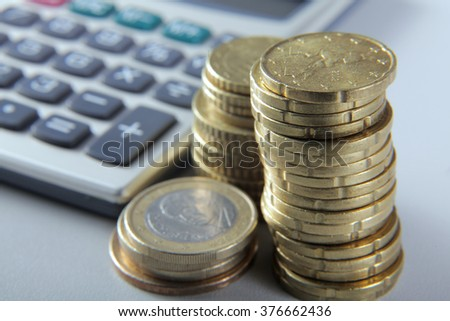 Coins and calculator on the desk - stock photo
