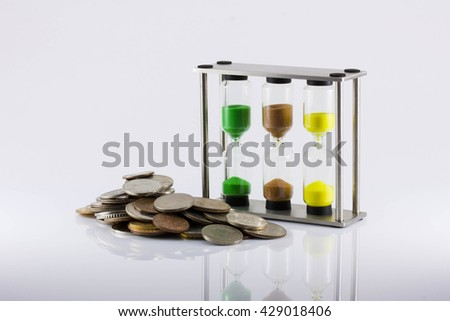 coins and hourglass on a white background. The increase in the price of labour, the growth of the man-hour cost, time cost, inflation, crisis, isolated - stock photo