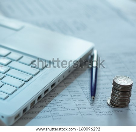 coins and pen near laptop - stock photo