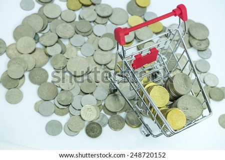 Coins and trolley with white background - stock photo