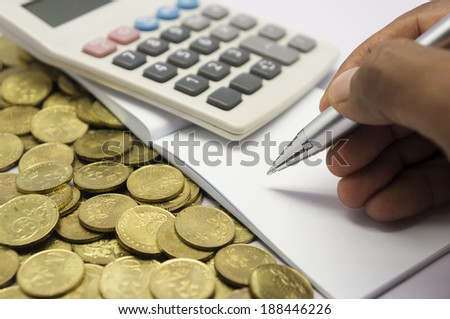 Coins, calculator, hand writing on paper with pen and white striped - stock photo