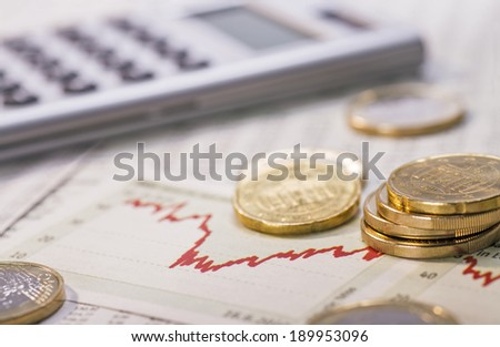 Coins, chart and calculator as a symbol for exchange rates. - stock photo