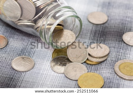 Coins falling from a glass bottle - stock photo