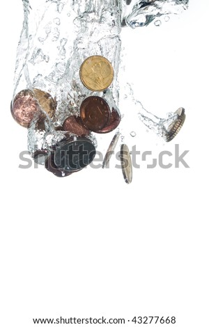 Coins falling into clear water - stock photo