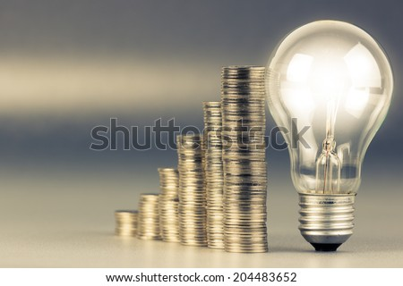 Coins heap stair with glowing light bulb - stock photo