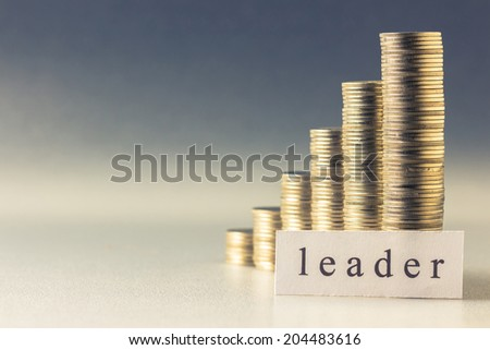 Coins heap stair with Leader topic printed on paper