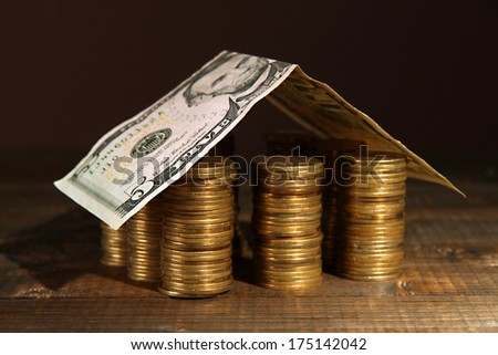 Coins house on table on brown background - stock photo