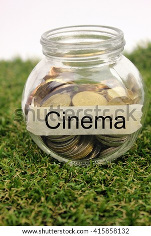 Coins in a glass container with a label cinema . Financial concept.