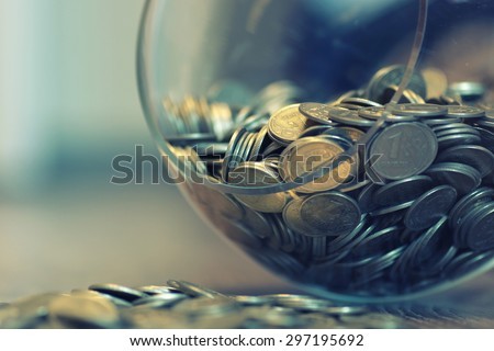 coins in a piggy bank vase - stock photo