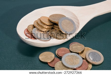 Coins in a wooden spoon on a green background - stock photo