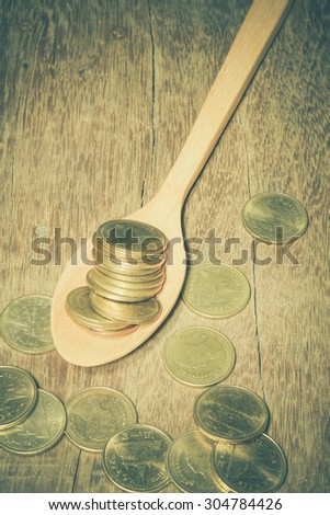 Coins in a wooden spoon with filter effect retro vintage style - stock photo