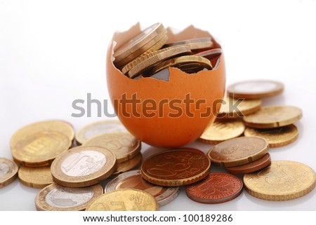 coins in an eggshell, metaphor for financial savings,fragile financials,...........