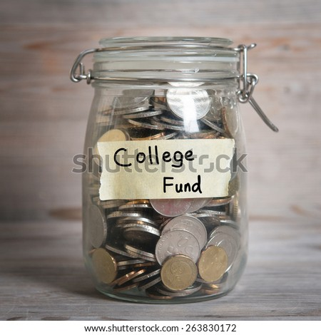 Coins in glass jar with college fund label, financial concept. Vintage wooden background with dramatic light. - stock photo