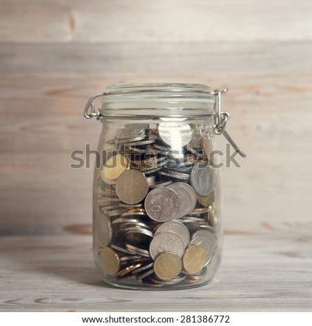 Coins in glass money jar, financial concept. Vintage wooden background with dramatic light. - stock photo