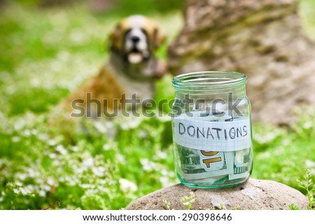 Coins in glass money jar with donations label, financial concept.  - stock photo