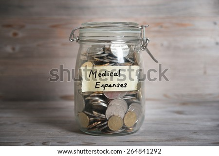 Coins in glass money jar with medical expenses label, financial concept. Vintage wooden background with dramatic light. - stock photo
