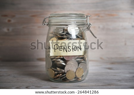 Coins in glass money jar with pension label, financial concept. Vintage wooden background with dramatic light. - stock photo