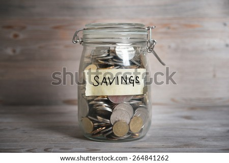 Coins in glass money jar with savings label, financial concept. Vintage wooden background with dramatic light. - stock photo