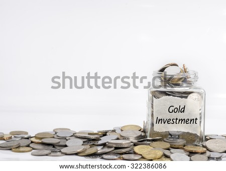 coins in jar with gold investment label in isolated white background; financial concept - stock photo