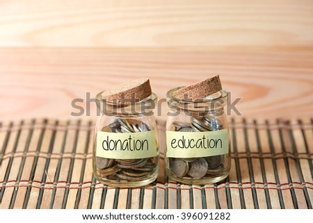 Coins in jar. Writing Donation Education on two jar with wooden pallet background. Selective focus with shallow depth of field. - stock photo