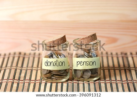 Coins in jar. Writing Donation Pension on two jar with wooden pallet background. Selective focus with shallow depth of field. - stock photo