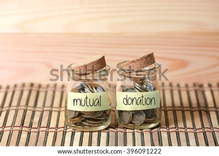 Coins in jar. Writing Mutual Donation on two jar with wooden pallet background. Selective focus with shallow depth of field. - stock photo