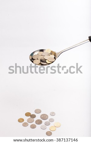 coins in ladle and a lot of coin on white background