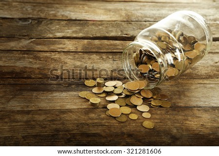 Coins in money jar on wooden background - stock photo