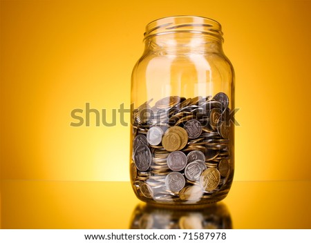 coins in money jar on yellow background - stock photo