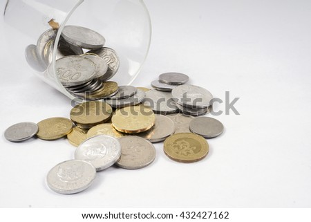 Coins in the glass isolated on white table. Business concept. DOF and copy space.