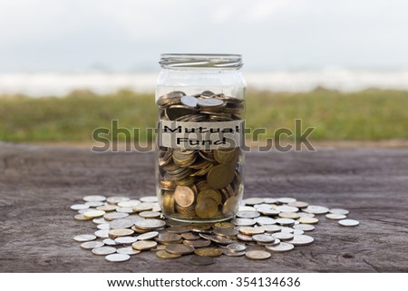 Coins in the jar or glass on the wood with MUTUAL FUND label against bokeh beach background. Financial concept. selective focus - stock photo