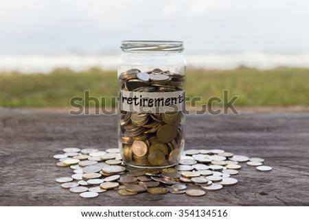 Coins in the jar or glass on the wood with RETIREMENT label against bokeh beach background. Financial concept. selective focus - stock photo