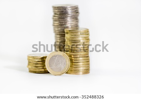 coins of 2 and 1 euros stacked and euro banknotes on a white background  - stock photo