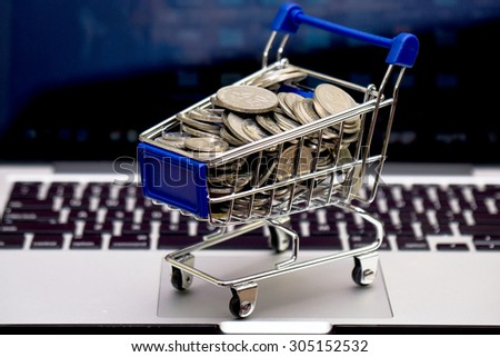 Coins of Malaysia in shopping cart trolley with keyboard notebook as background - stock photo