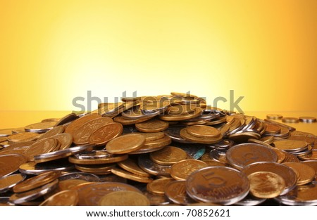 Coins on yellow background - stock photo