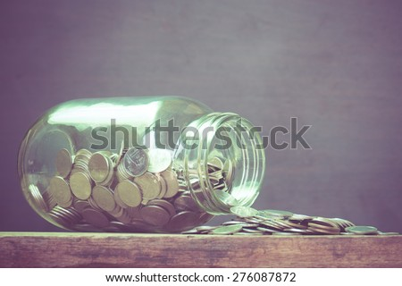 Coins spilling out of a glass bottle with filter effect retro vintage style - stock photo