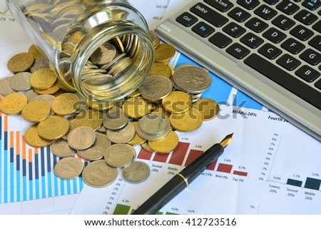 Coins spilling out of jar on the business stock charts - Business Concept