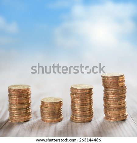 Coins stack in row on wooden background, financial concept. Focus on foreground with blur blue sky background. - stock photo