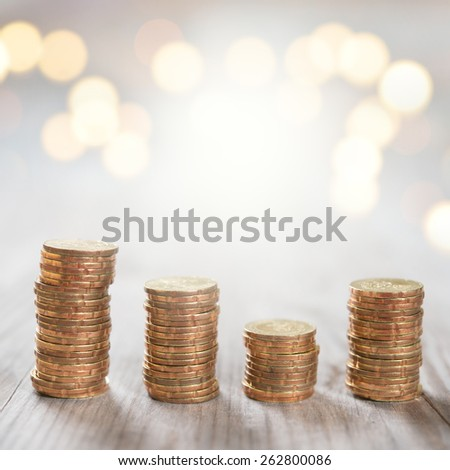 Coins stack in row on wooden background, financial concept. Focus on foreground with blur shinny background. - stock photo