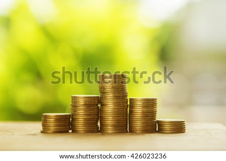 coins stack with natural green leaf background