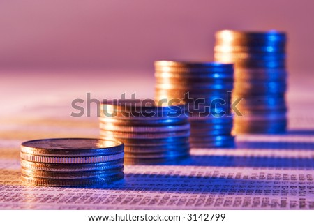 Coins stacked as a rising graph on stock report - stock photo