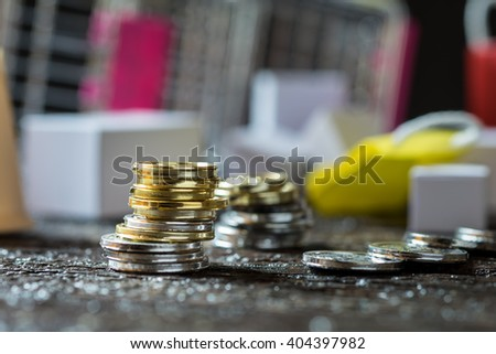 Coins stacked on each other in different positions. Money concept. Shopping trolley. Shopping cart in the background - stock photo