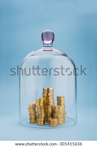 Coins stacks protected under a glass dome on blue background - stock photo